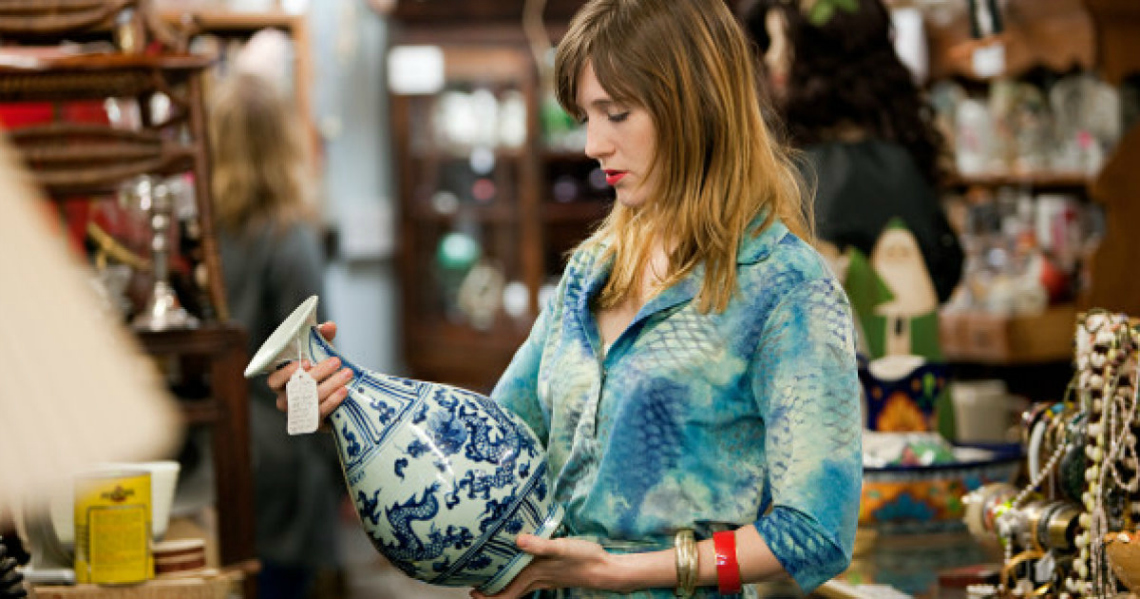 Woman inspecting vase in thrift shop